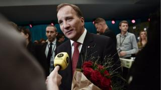 Swedish PM Stefan Lofven talks to the press, carrying red roses, after a TV debate on 7 September 2018