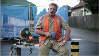 Man dressed as tradesman speaks in still from an advertisement