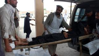 An Afghan wounded man lays on a trolley as others rush him to a hospital following a blast at a voter registration centre in Khost Province on 6 May 2018