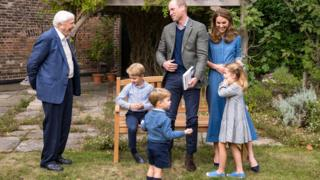 The Duke and Duchess of Cambridge, Prince George (seated), Princess Charlotte and Prince Louis with Sir David Attenborough in the gardens of Kensington Palace