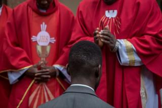 Bobi Wine is seen kneeling in front of two priests.