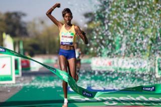 Kenyan runner Purity Rionoripo celebrates winning the 41st Paris Marathon in Paris