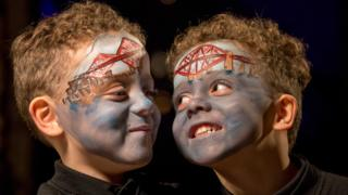 Smiling boys with forth bridges painted on their faces