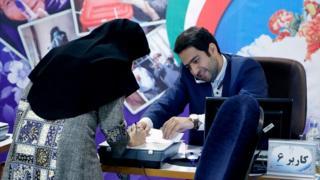 Mujer registra su voto en Teherán
