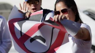 A Venezuelan in Honduras rips a sign depicting Nicolas Maduro
