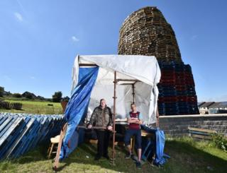 Brothers Mark (L) and Hayden (R) watch over the nearly completed bonfire on the Ballyduff estate from their makeshift shelter on July 10, 2017 in Newtownabbey, Northern Ireland.