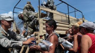 "Soldiers of Puerto Rico""s national guard distribute relief items to people, after the area was hit by Hurricane Maria in San Juan, Puerto Rico September 24, 2017"