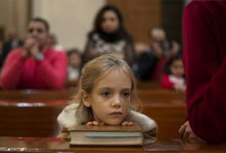 Девочка слушает рождественскую проповедь в церкви в Каире