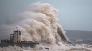Waves crash over the cost in Porthcawl, Wales, as Storm Brian hits the UK