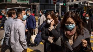 Residents wear surgical mask as they cross a street in a shopping district