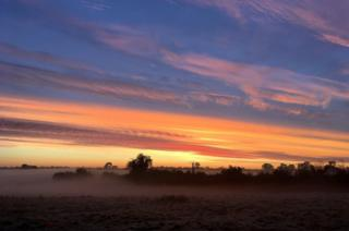 View of sunrise over fields with morning mist