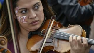 in_pictures A musician of the conservatory of the National University of Colombia plays the violin with her face painted that reads