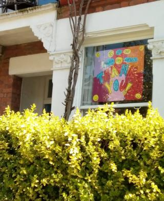 A colour picture in a window behind a hedge