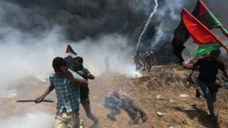 Palestinian demonstrators run for cover during a protest against U.S. embassy move to Jerusalem