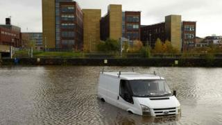 An abandoned van is pictured in flood water near residential buildings in Rotherham, northern England on November 8, 2019, following flash flooding