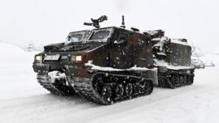 A track vehicle of the German armed forces Bundeswehr drives through the snow to supply the cut off Buchenhoehe settlement area in Berchtesgaden, southern Germany, on January 10, 2019