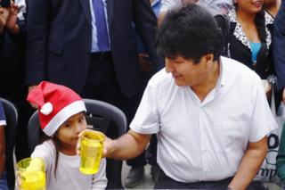 in_pictures Exiled former president of Bolivia Evo Morales talks to a girl during a Christmas breakfast with members of the Bolivian community of Buenos Aires at Campo De Deportes del Colegio Nacional de Buenos Aires on 25 December 2019 in Buenos Aires, Argentina