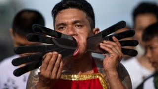 Devotee with several knives piercing his cheeks