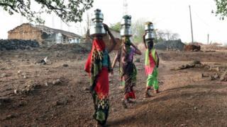 Mulheres retornam a suas ideias levando água na aldeia de Rahatgarh, no Estado de Madhya Pradesh