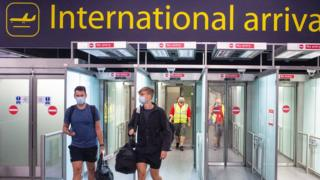 Masked passengers arriving at Gatwick airport