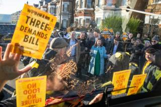 Jo Swinson speaks to Extinction Rebellion protesters dressed as bees glued to a bus