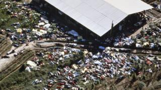Hundreds of figures are photographed strewn round the building in aerial shot of Jonestown site