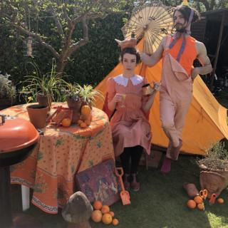 Helen Yang and Thomas Etheridge in orange outfits