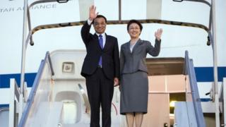Chinese Prime Minister Li Keqiang (L) and his wife Cheng Hong wave to officials upon their arrival at the Charles De Gaulle airport in Roissy, Suburban Paris on June 29, 2015.