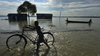 A boy pushing a bicycle through flood water with huts and a tree in the background