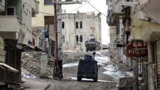 Military vehicles drive through a deserted street of Silvan, south-east Turkey, during a curfew following clashes between Turkish forces and Kurdish militants