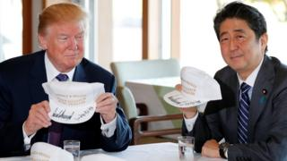特朗普(前左)与安倍晋三(前右)展示各自的纪念鸭舌帽(5/11/2017)