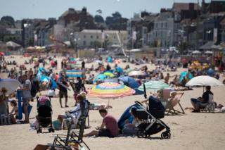 People enjoy the sunny weather at a beach at Weymouth seafront in Dorset, England