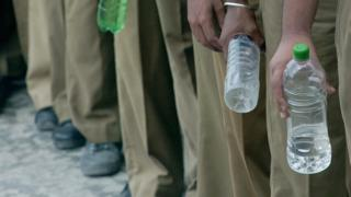 Indian schoolboys clutch water bottles as they stand in line as part of an earthquake drill taking place at their school in Port Blair, 06 January 2005.