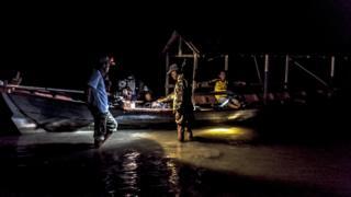 Members of Trapang Sangke community prepare their boat