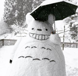 Şemsiye taşıyan Totoro karakterinin kardan heykeli