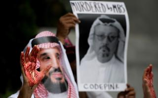 A demonstrator dressed as Saudi Arabian Crown Prince Mohammed bin Salman with blood on his hands protests outside the Saudi Embassy in Washington DC, October 2018
