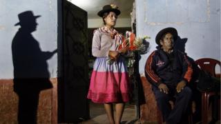 Una mujer sostiene una ofrenda de flores en memoria a los muertos de Cayara. (Foto: Ángela Ponce)