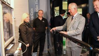 Prince Charles presses the button to strike the coin