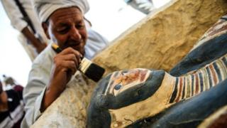 A man brushes off dust from a sarcophagus, part of a new discovery carried out near the King Amenemhat II's pyramid at Dahshur. Photo: 13 July 2019