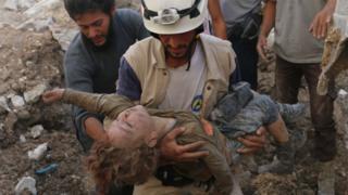Спасатель с телом девочки, извлеченной из под обломков здания
