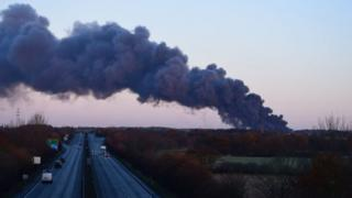 Plume of smoke near the motorway caused by fire