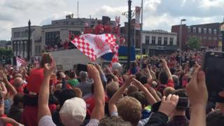 Barnsley players on a bus surrounded by fans