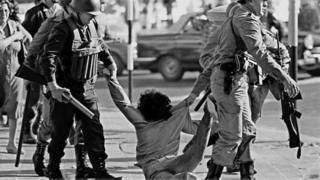 Dos militares arrastrando a un ciudadano por el piso.