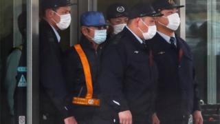 Carlos Ghosn (in the blue hat) leaving prison