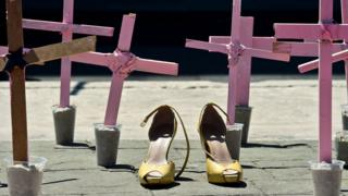 A pair of high heeled shoes in the middle of pink crosses