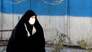 A woman wearing a face mask walks down a street in Tehran (2 March 2020)