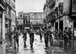 British troops in Calcutta, with rifles at the ready, clearing a street after Hindus and Muslims used firearms against each other