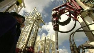 Man looking up at fracking equipment