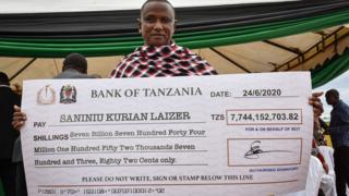 Tanzanian small-scale miner Saniniu Kuryan Laizer, 52, poses with the enlarged cheque copy from the government after selling two of the biggest of the country's precious gemstones, Tanzanite, during the ceremony for his historical discovery in Manyara, northern Tanzania - 24 June 2020