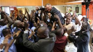 Workers celebrate with Radisson Blu hotel manager Gary Ellis after the hotel reopened in Bamako, Mali, 15 December